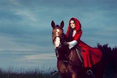 Hood Princess Riding rojo un caballo imagenes de archivo