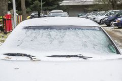 Hood and windshield of a parked car covered with first snow stock image