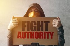 Hooded activist protestor holding Fight authority protest sign. Man with hoodie and scarf over face taking part in activism and fighting for the cause stock photos