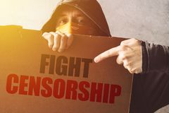 Hooded activist protestor holding Fight censorship protest sign. Man with hoodie and scarf over face taking part in activism and fighting for the cause royalty free stock image