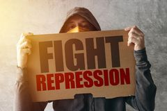 Hooded activist protestor holding Fight repression protest sign. Man with hoodie and scarf over face taking part in activism and fighting for the cause royalty free stock photos