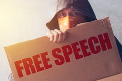 Hooded activist protestor holding Free Speech protest sign. Man with hoodie and scarf over face taking part in activism and fighting for the cause royalty free stock photography