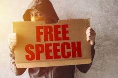 Hooded activist protestor holding Free Speech protest sign. Man with hoodie and scarf over face taking part in activism and fighting for the cause stock photo