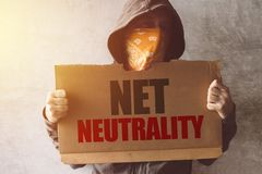 Hooded activist protestor holding Net neutrality protest sign. Man with hoodie and scarf over face taking part in activism and fighting for the cause royalty free stock images