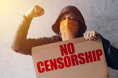 Hooded activist protestor holding No Censorship protest sign. Man with hoodie and scarf over face taking part in activism and fighting for the cause royalty free stock photos