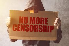 Hooded activist protestor holding No More Censorship protest sign. Man with hoodie and scarf over face taking part in activism and fighting for the cause royalty free stock images