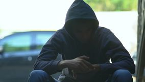Hooded Afro-American teen boy suffering withdrawal symptoms, drug addiction. Stock footage stock video