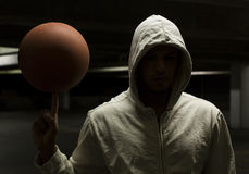 Hooded anonymous basketball player spinning a ball. A basketball player spins the ball whilst under a street light Stock Photography