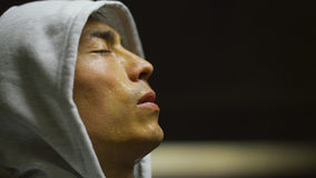 Hooded athlete regaining his breath after a workout Stock Image