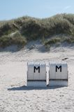 Hooded beach chairs. Signed with an M Royalty Free Stock Images