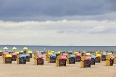 Hooded beach chairs strandkorb at Baltic seacoast in Travemunde, Germany royalty free stock photography