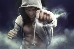 Hooded boxer punching an enemy. Hooded muscular boxer punching an enemy Stock Photography