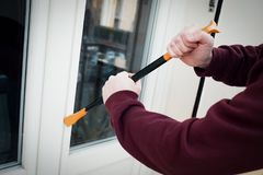 Hooded burglar forcing window lock to make a theft in a house. Burglar forcing window to rob in the house royalty free stock photography