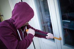 Hooded burglar forcing window to rob in the house. Hooded burglar forcing window lock to make a theft in a house royalty free stock photo