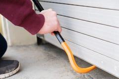 Hooded burglar forcing window shutter lock royalty free stock photography
