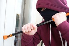 Hooded burglar forcing window to rob in the house. Hooded burglar forcing window lock to make a theft in a house Royalty Free Stock Photography