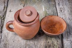 Clay pot with clay cup on old grunge table. Hooded clay pot with clay cup on old grunge table Royalty Free Stock Photos