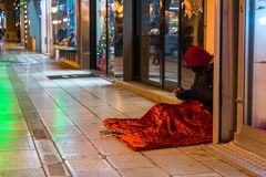 Hooded Clochard In A Street Near A Window Of A Shop During A Col stock photography