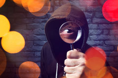 Hooded computer hacker with magnifying glass Stock Photos
