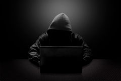 Hooded computer hacker stealing information. With laptop Royalty Free Stock Photos
