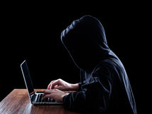 Hooded computer hacker stealing information Royalty Free Stock Image