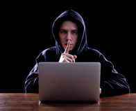 Hooded computer hacker stealing information Stock Images