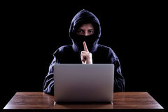 Hooded computer hacker stealing information Royalty Free Stock Photography