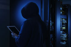 Hooded computer hacker stealing information with Tablet PC Stock Photos