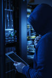 Hooded computer hacker stealing information with Tablet PC. Server in the background Stock Image