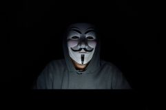 A hooded computer hacker. Wearing a V for Vendetta or anonymous mask Royalty Free Stock Photography