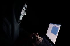 A hooded computer hacker. Wearing a V for Vendetta or anonymous mask stock photos