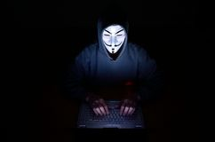A hooded computer hacker. Wearing a V for Vendetta or anonymous mask Royalty Free Stock Images
