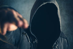 Hooded criminal gesturing gun shooting with fingers Stock Photos