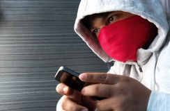 Hooded cyber crime hacker using mobile phone internet hacking. In to cyberspace,online personal data security concept Stock Photos