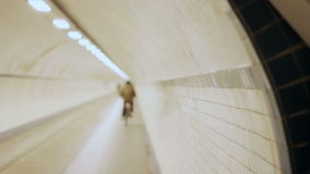Hooded Cyclist Fades Away in Tunnel in Slow Motion stock video footage