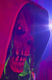 Hooded Demon. Scary hooded demon figure with colored light and flare Royalty Free Stock Photo