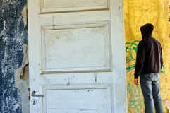 Hooded figure. In abandoned house. Empty room weathered walls torn wallpaper Stock Photos