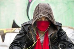 Hooded figure. Wearing a scarf in front of his nose and mouth to disguise himself, looking menacing into the camera stock images