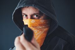 Hooded gang member criminal with gun stock image