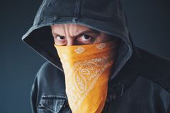 Hooded gang member criminal with scarf over face. Looking at camera royalty free stock photo