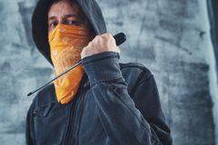 Hooded gang member criminal with screwdriver. Hooded gang member criminal with scarf over face with screwdriver as weapon royalty free stock image