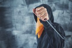 Hooded gang member criminal with screwdriver. Hooded gang member criminal with scarf over face with screwdriver as weapon stock photos