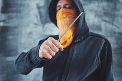 Hooded gang member criminal with screwdriver. Hooded gang member criminal with scarf over face with screwdriver as weapon stock photo