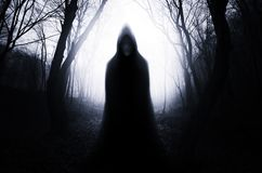 Hooded ghost in haunted forest with fog on Halloween night. Hooded ghost monster in haunted forest with fog on Halloween. Haunted dark spooky scary mysterious royalty free stock photos