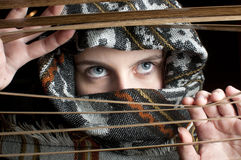 Hooded girl behind shades. A girl with a hood looking behind shades Royalty Free Stock Photos