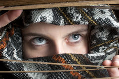 Hooded girl looking through window blinds Royalty Free Stock Photography