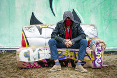 Hooded graffiti artist. Young man with an attitude sitting with a scarf over his mouth to disguise himself on a graffiti clad couch in front of a concrete, spray Stock Images