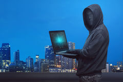 Hooded hacker with anonymous mask typing on laptop Royalty Free Stock Photography