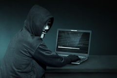 Hooded hacker with anonymous mask using laptop to steal data Royalty Free Stock Image