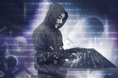 Hooded hacker man with vendetta mask typing on virtual keyboard Royalty Free Stock Image
